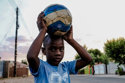 Boy Carrying Soccer Ball on His Head