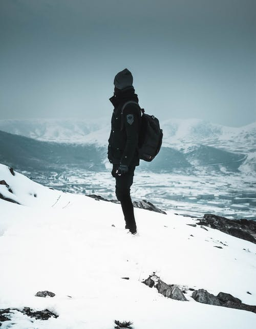 Person Standing on Snow Capped Mountain