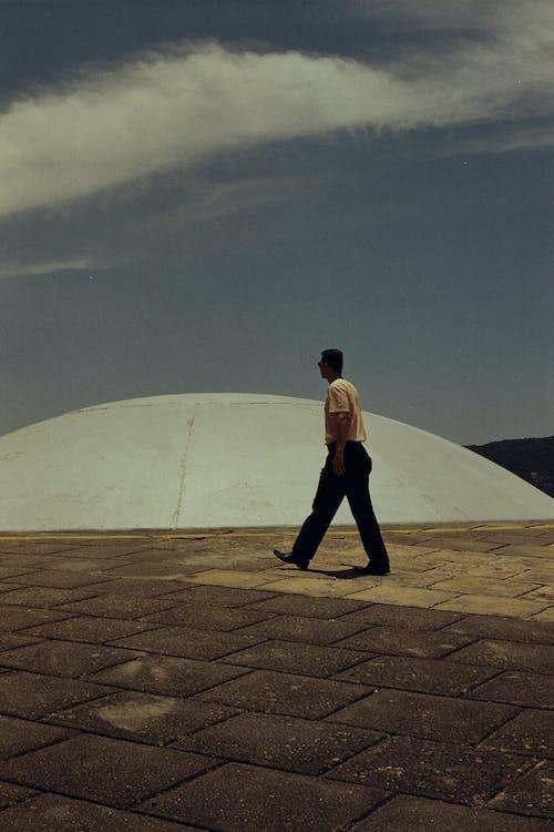Photo of Man Walking Near Stone Dome