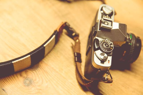 Black Camera With White and Black Strap on Beige Surface