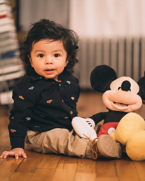 Sitting Child Playing Mickey Mouse Plush Toy