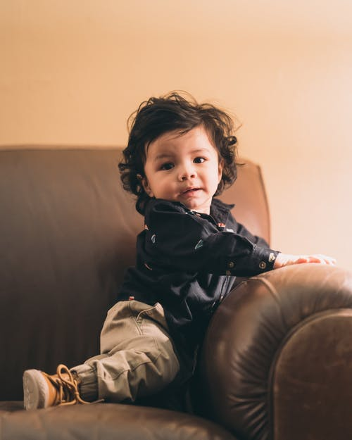 Toddler on Brown Sofa