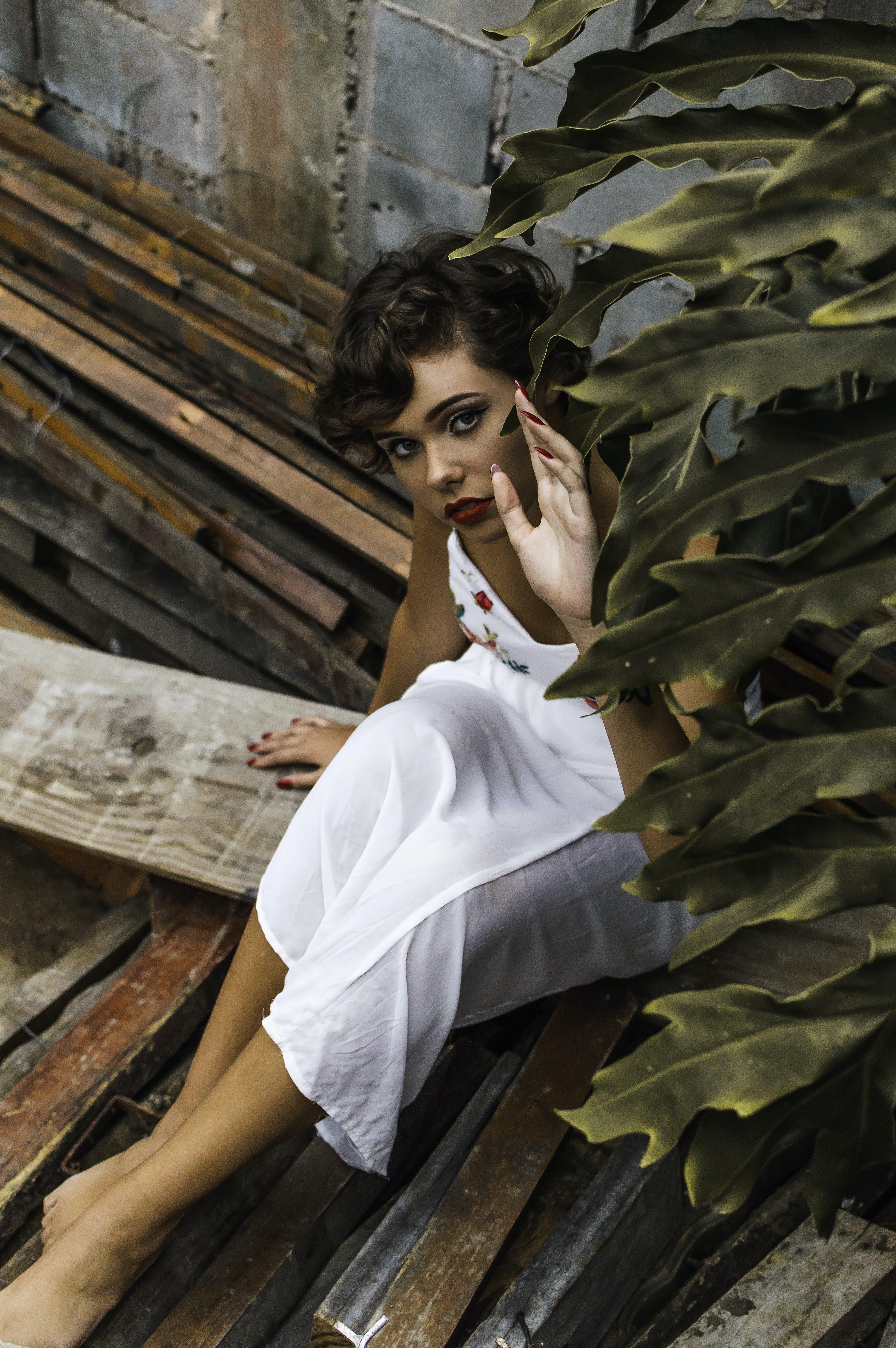 Woman Wearing Dress While Sitting on Lumber