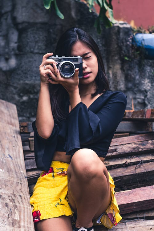 Woman Taking Photo Using SLR Camera