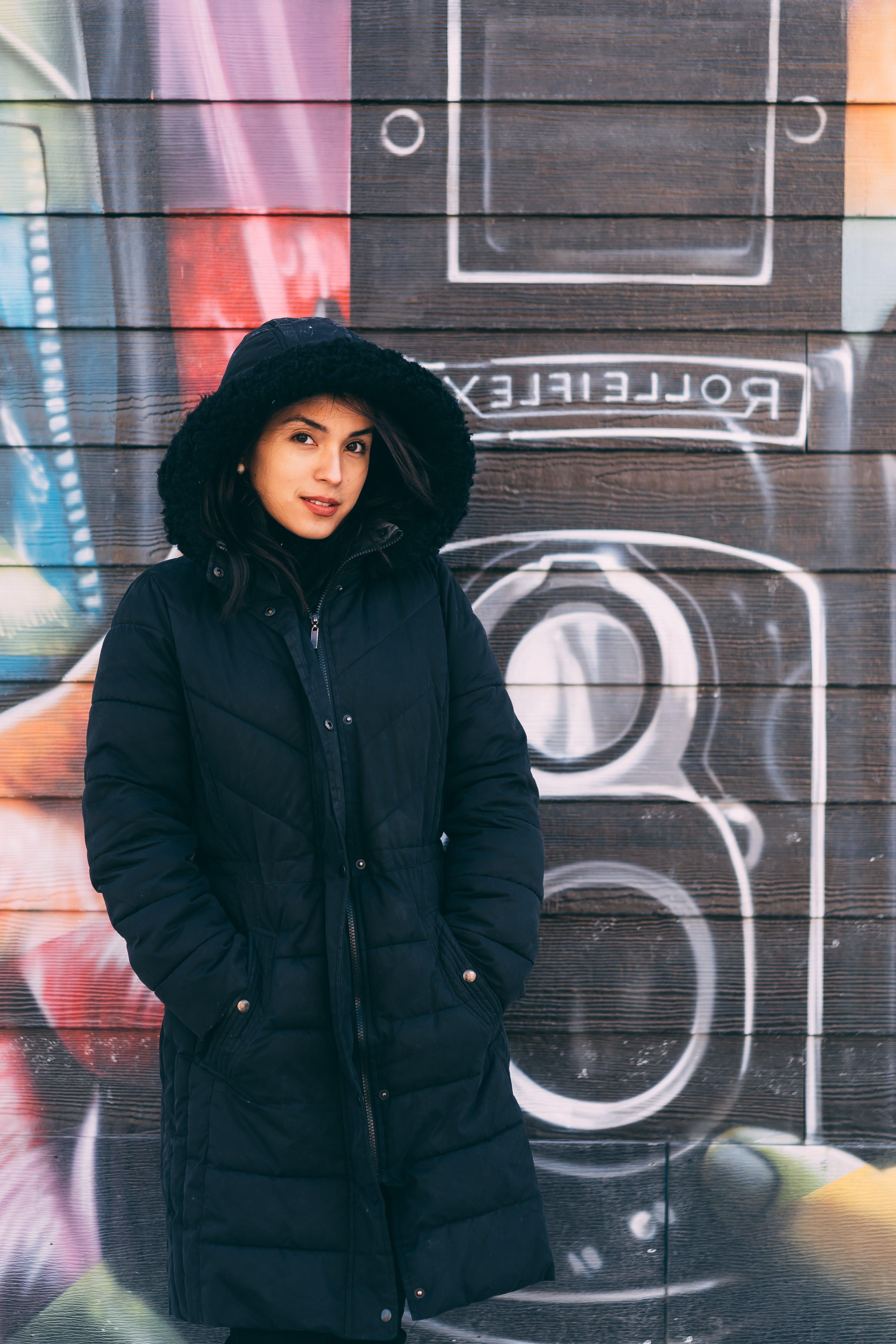 Woman Wearing Winter Jacket in Front Graffiti Wall