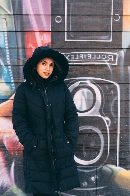 Frau, Die Winterjacke In Der Vorderen Graffiti Wand Trägt