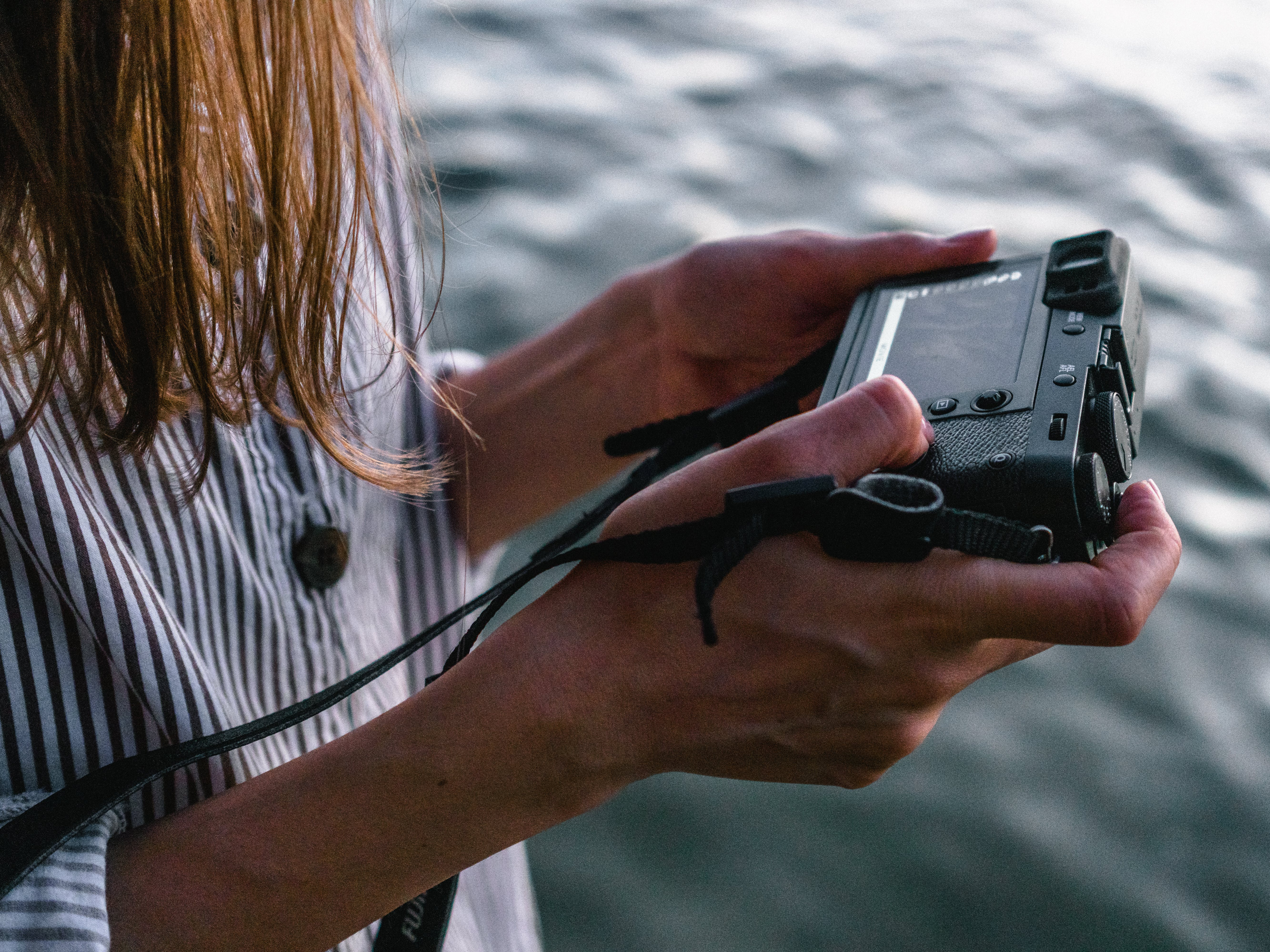 Close-up Photo of Woman Viewing Photos from Her Camera Near Body of Water