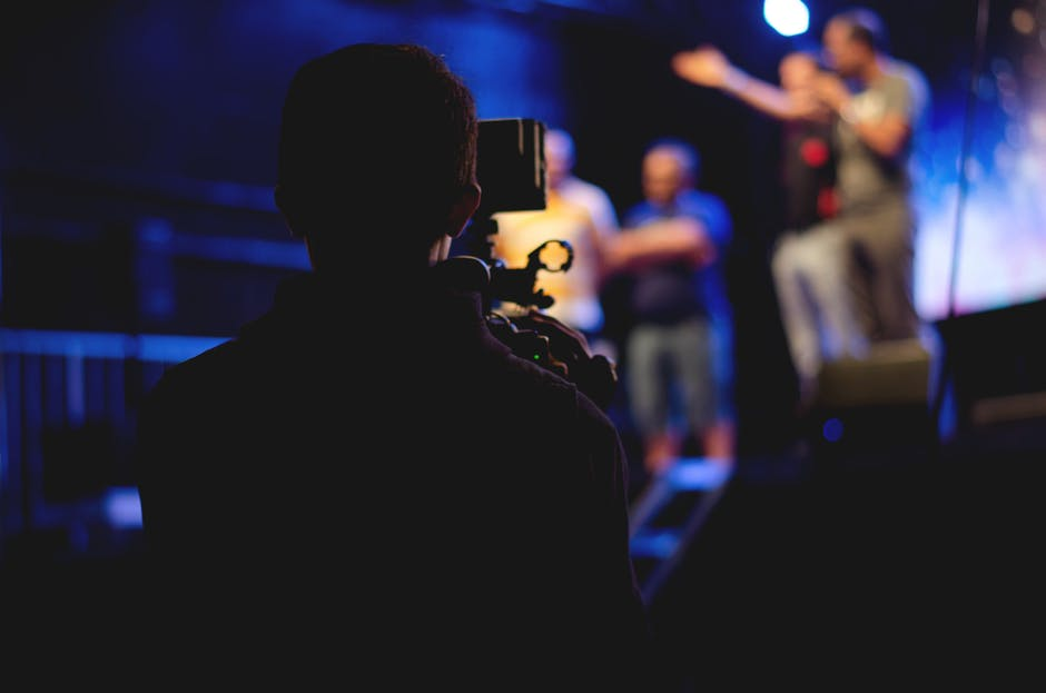 Man standing on stage holding microphone
