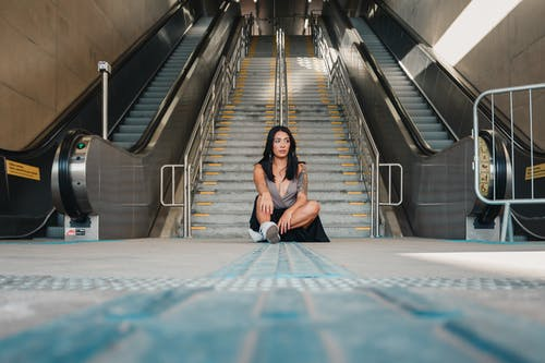 Photo of Woman Sitting on the Ground with Gray Concrete Stairs and Escalators in the Background