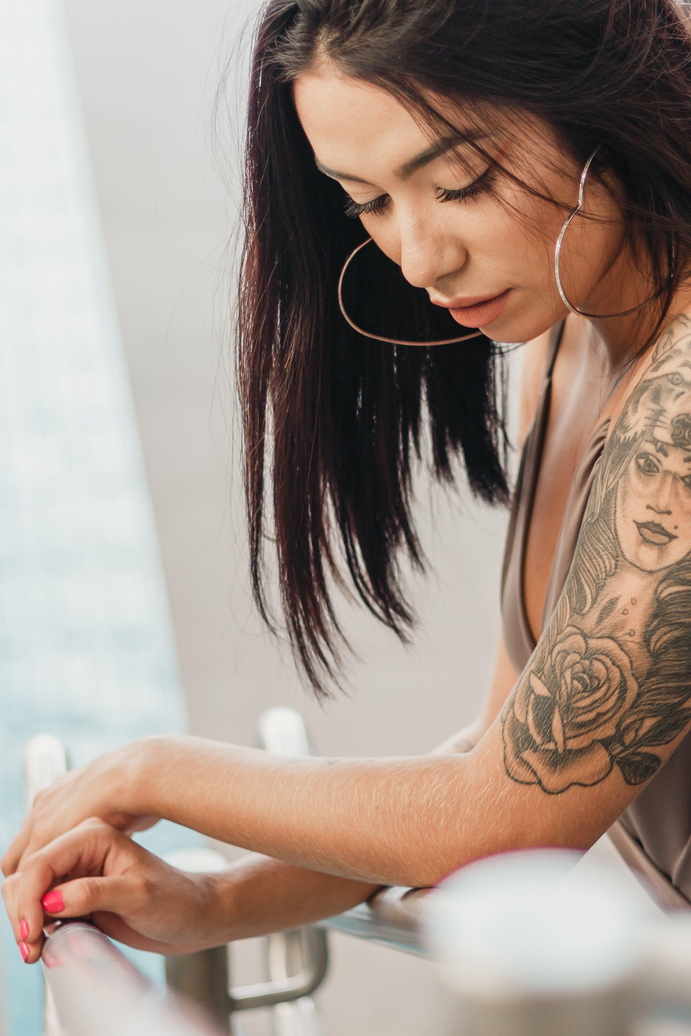 低頭看, 刺青的, 咖啡色頭髮的女人, 女人 的 免费素材照片