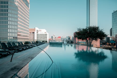 Бесплатное стоковое фото с город, здания, плавательный бассейн, шезлонги