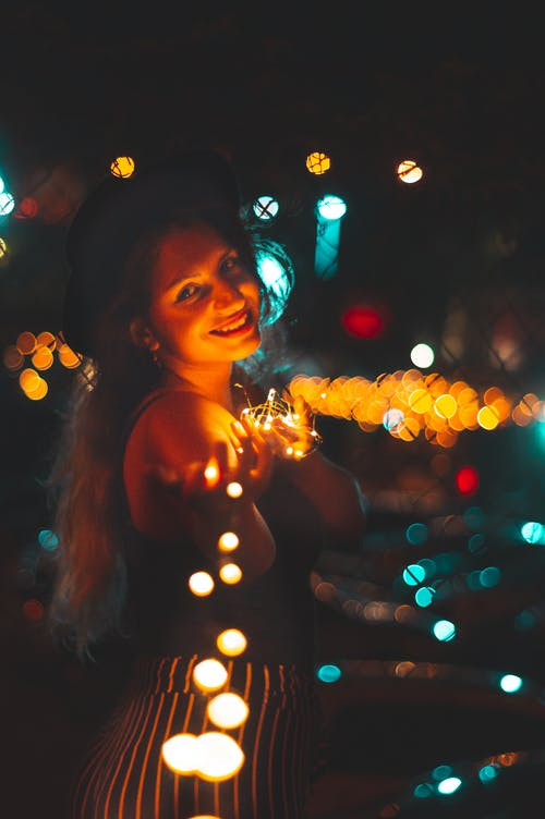 Selective Focus Photography Of Woman Holding String Lights
