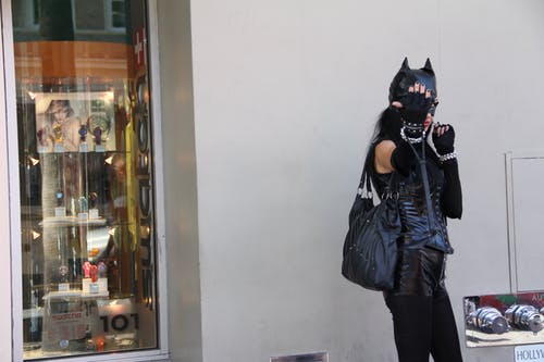Woman Leaning on Wall Wearing Black Cat Costume