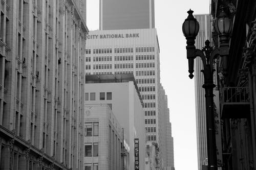 Grayscale Photo of Lamp Post and Buildings