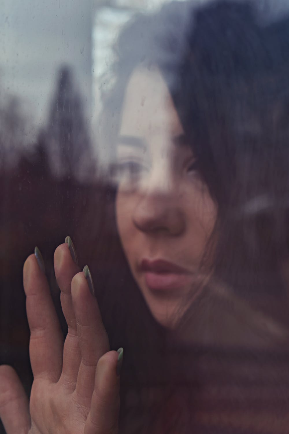 A sad woman touching the window | Photo: Pexels