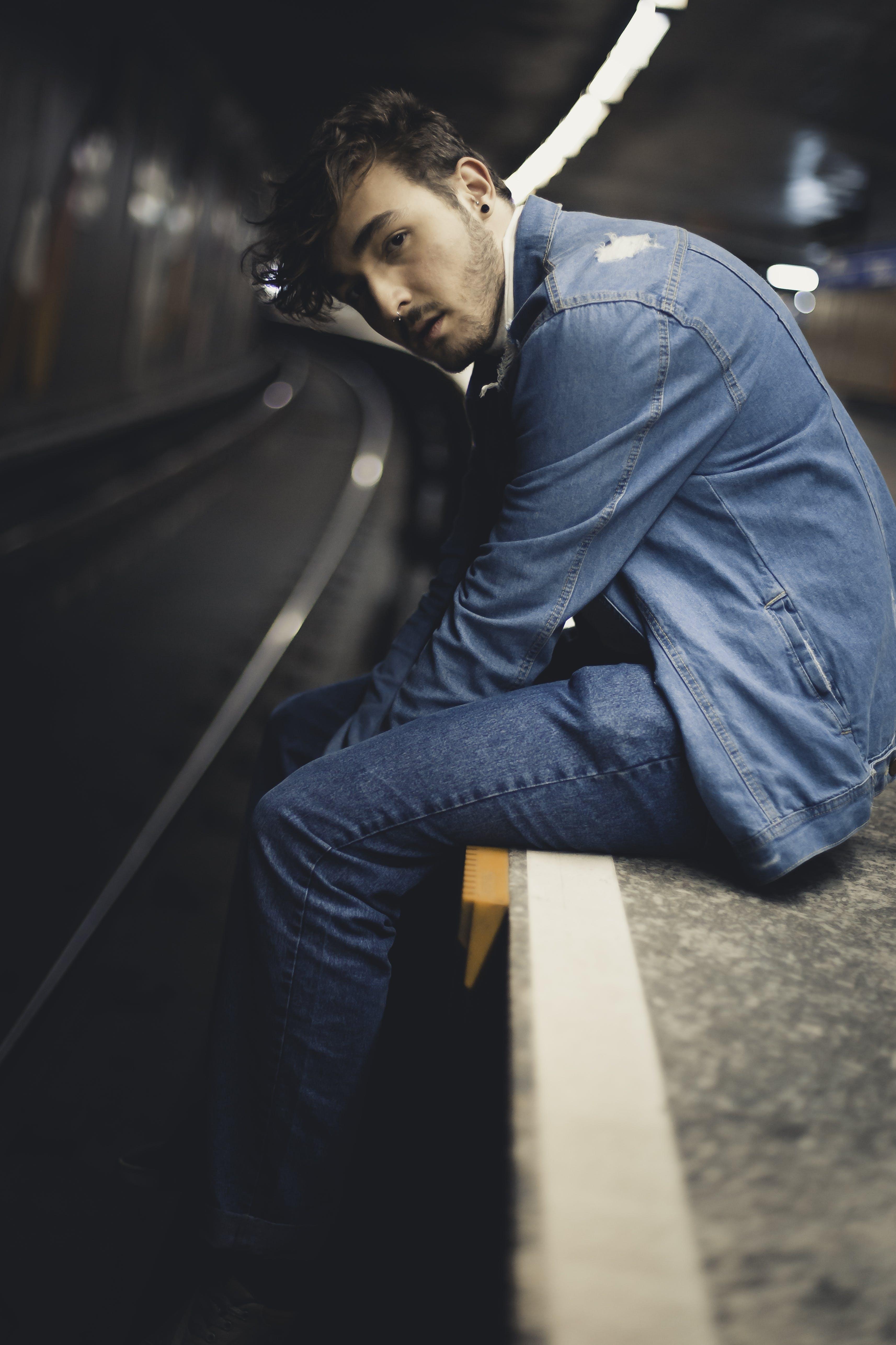 Man Wearing Blue Denim Jacket and Blue Denim Jeans Sitting on Gray Surface