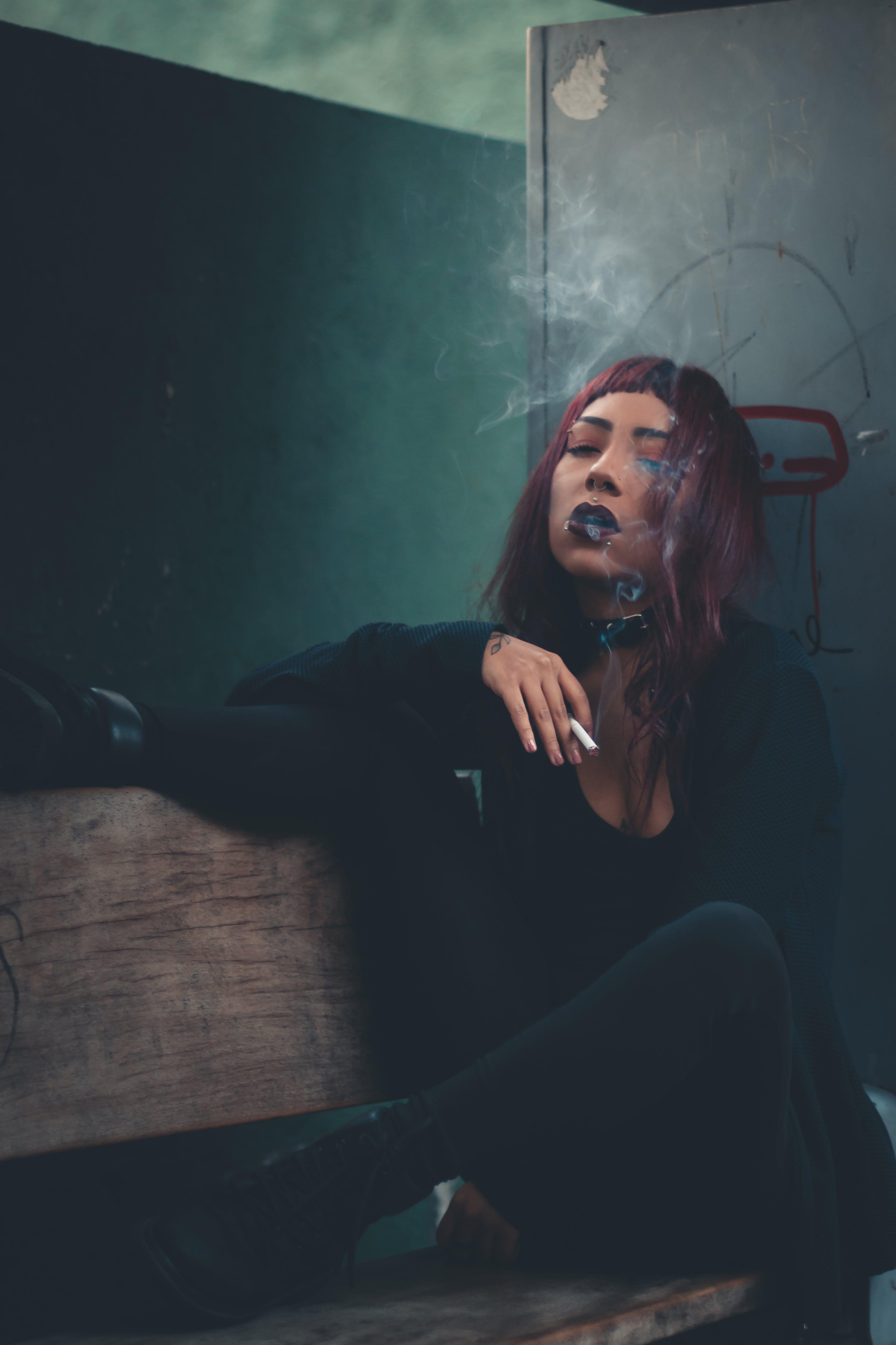Woman in Black Shirt Sitting and Smoking
