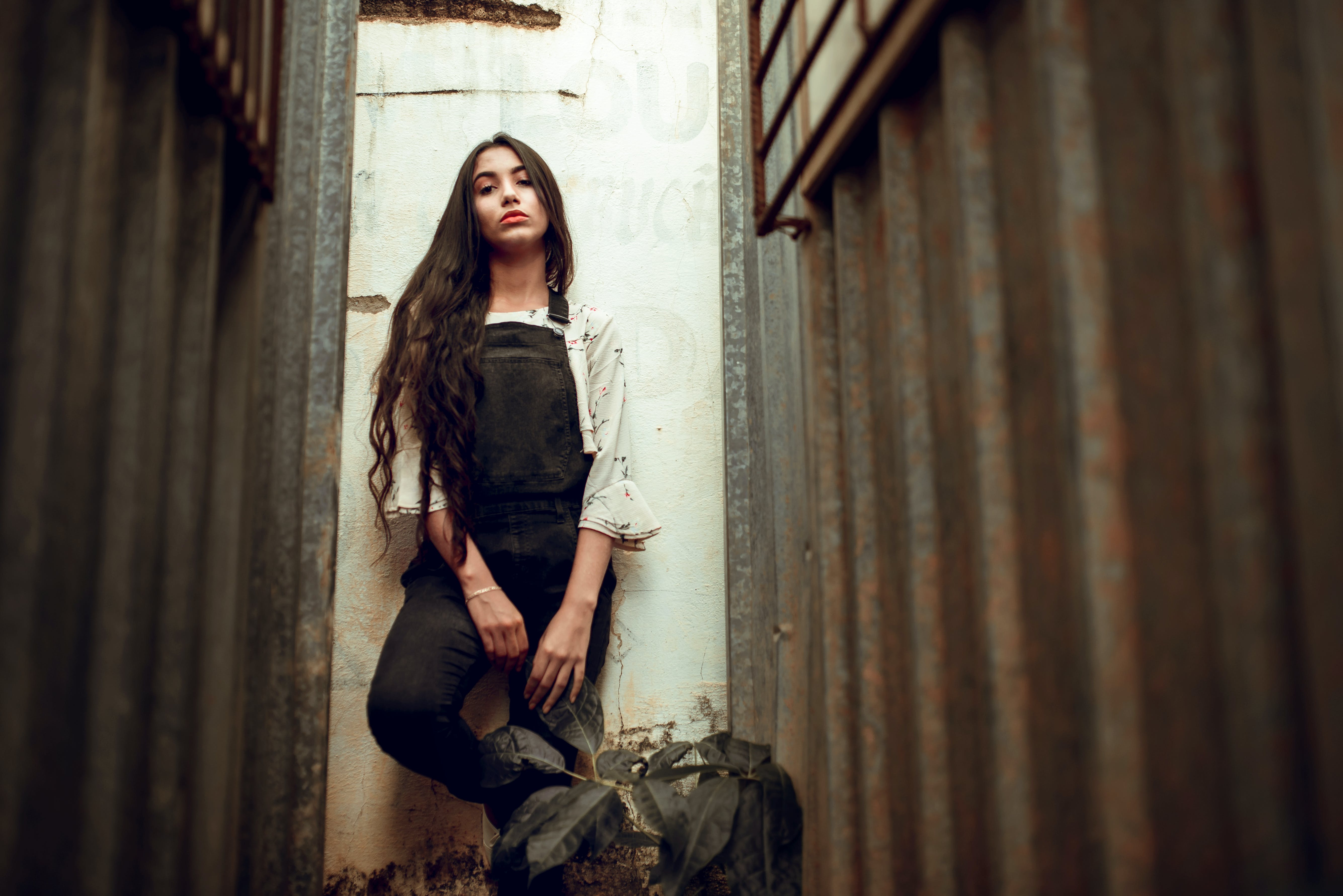Woman In Black Overalls Standing Against Wall