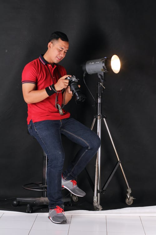 Man Sitting on Bar Chair Holding Camera Beside on Lights With Stand