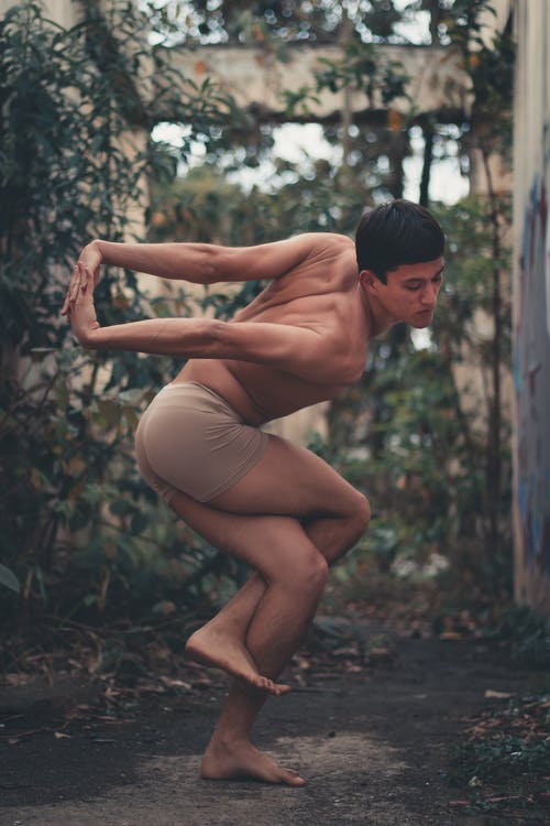 Man in Brown Boxer Shorts Doing Some Yoga Stretching