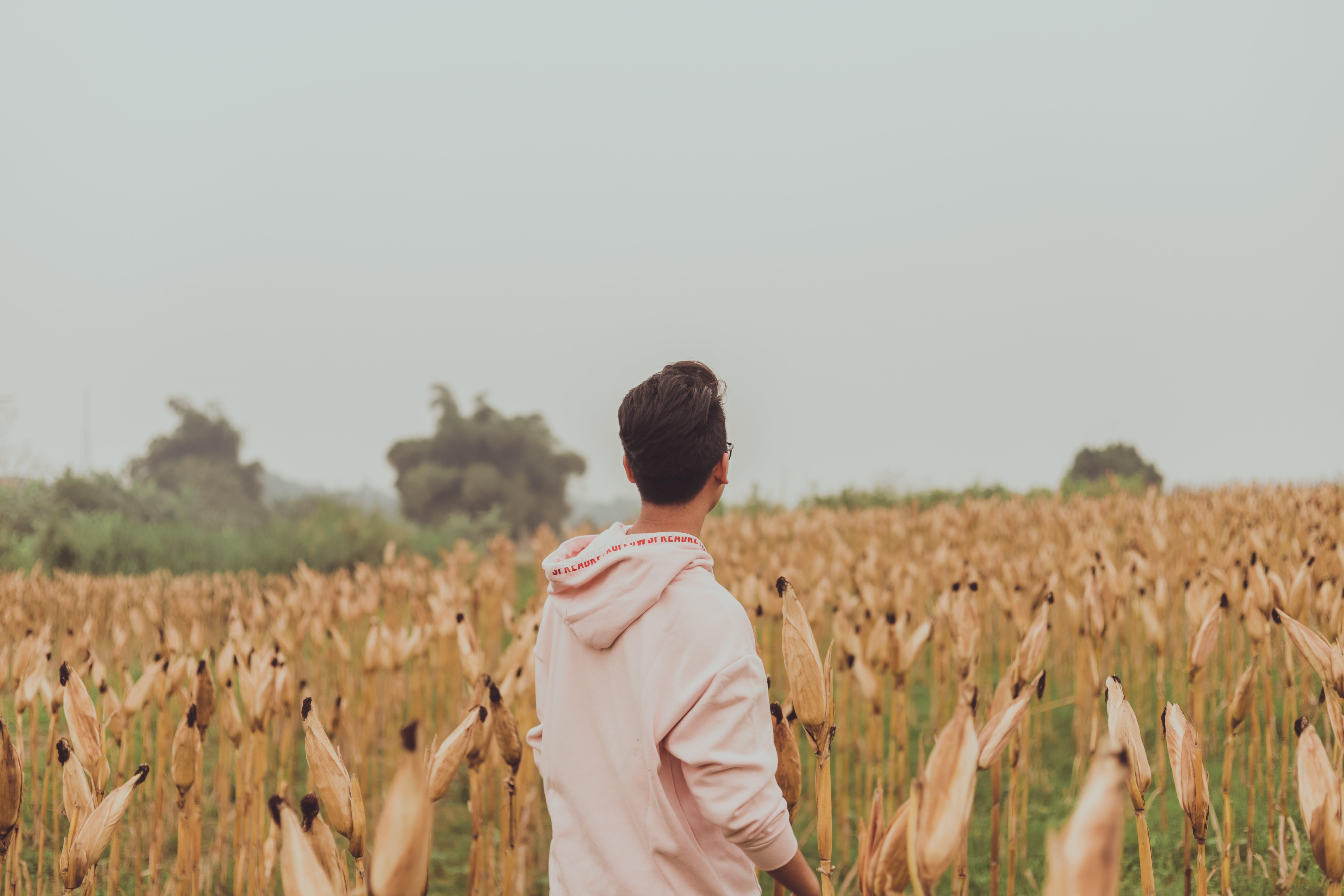 Man in White Hoodie Standing on White Grass Field
