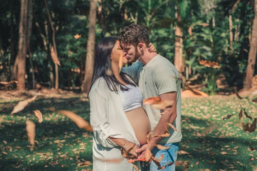Pregnant Woman and Man Kissing Front of the Tree