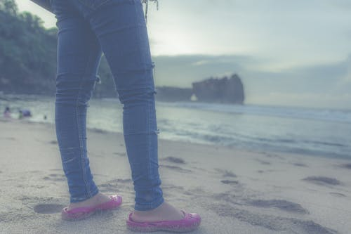 Person in Blue Jeans and Pink Flats in Front of Seashore