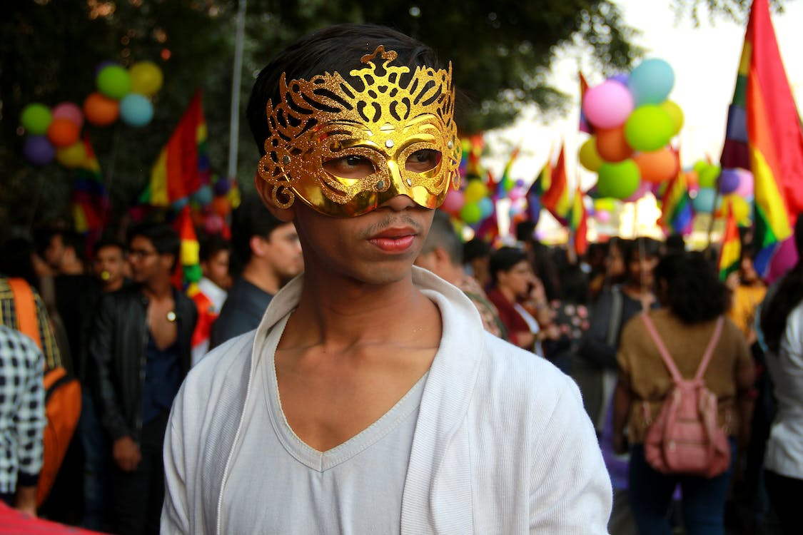 Man Wearing Gold Mask And White Shirt Surrounded by People