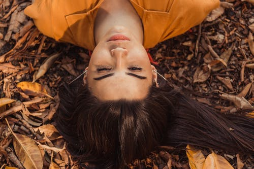 Woman Lying on Ground With Dried Leaves