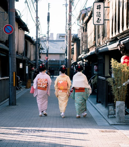 Three Woman Wearing Traditional Dresses Walking On Street