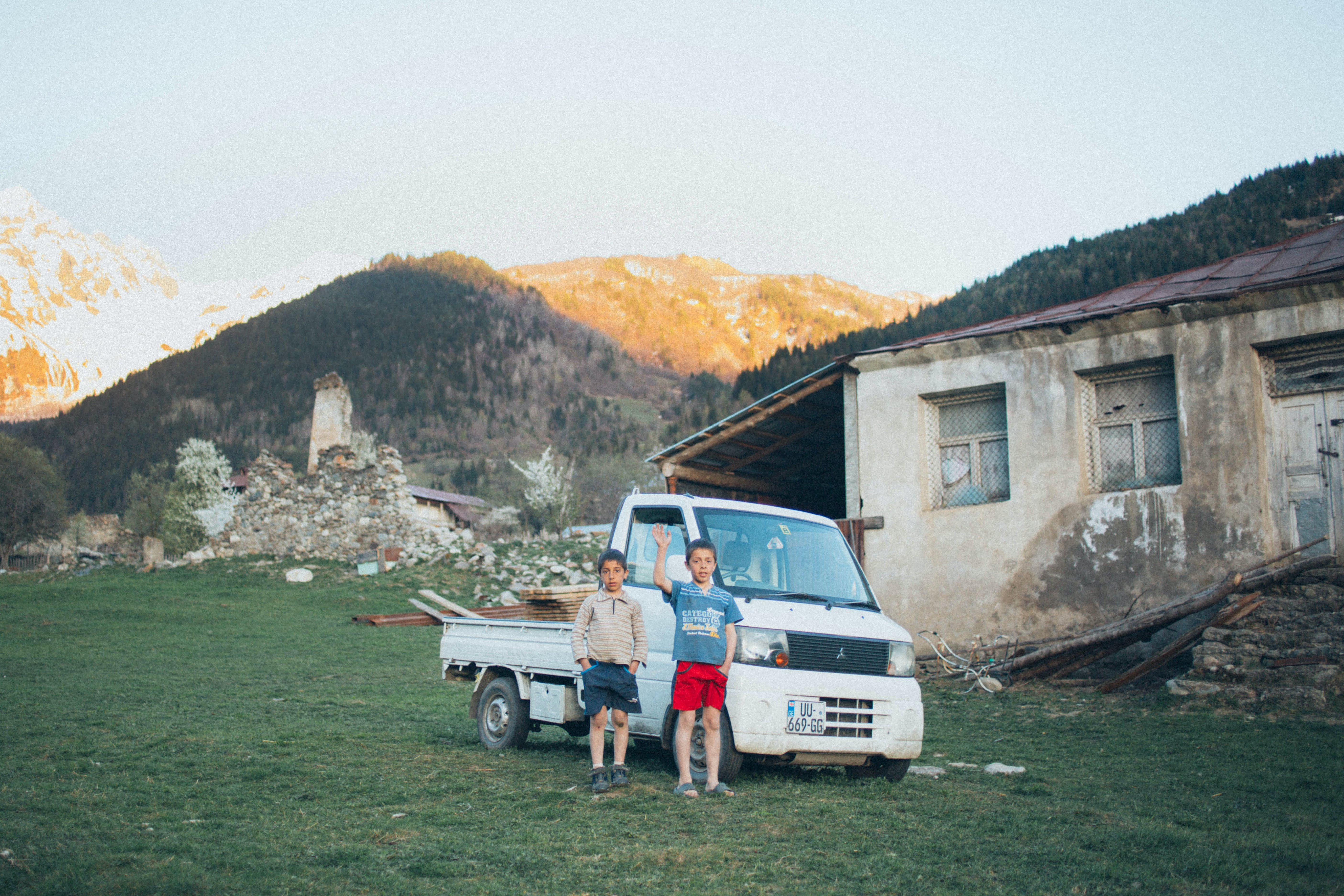 Two Boys Standing In Front Of Dropside Truck