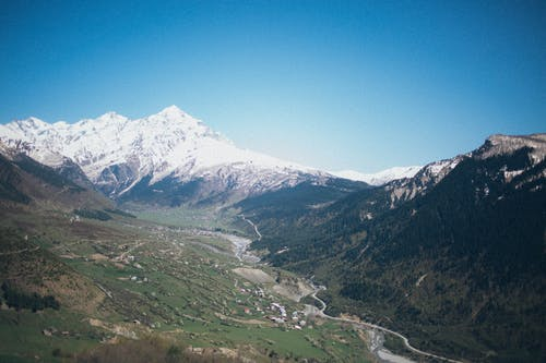 Aerial Photography of Valley and Snow Capped Mountains