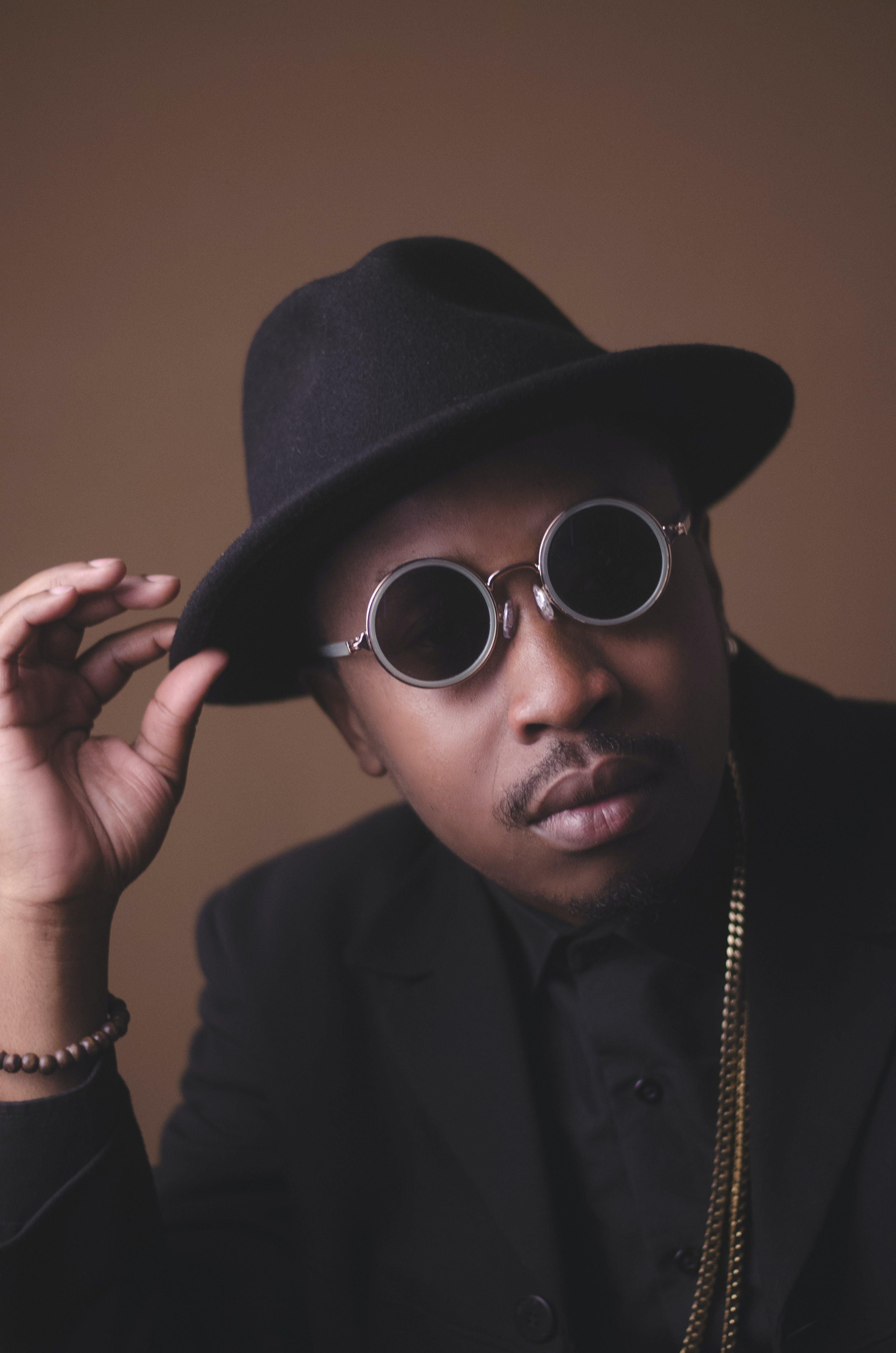 Man Holding Black Fedora Hat While Wearing Sunglasses