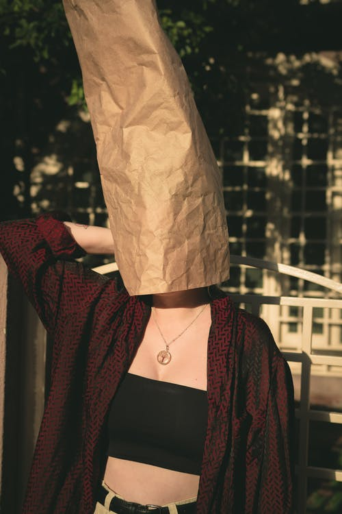 Person In Black Tube Top Covering Head With Paper Bag