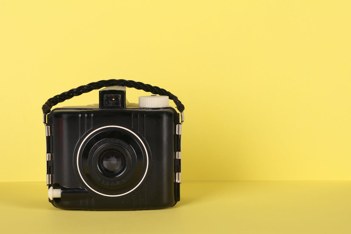 Black Camera On Yellow Surface