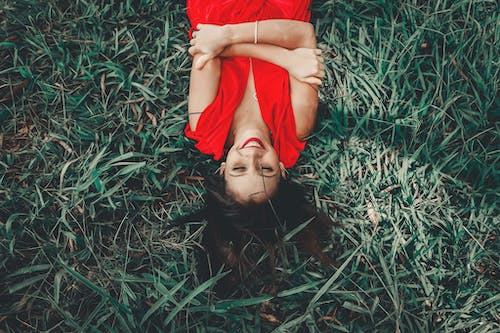 Woman Laying On Green Grass Field