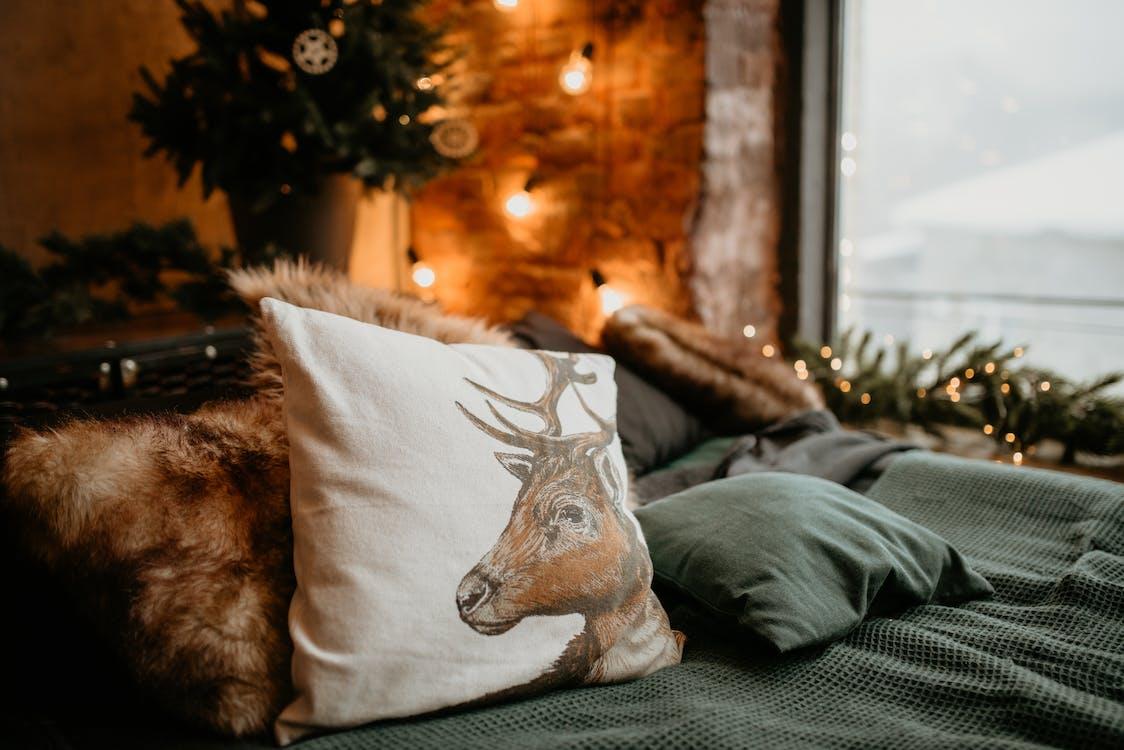 White and Brown Throw Pillow on Gray Textile