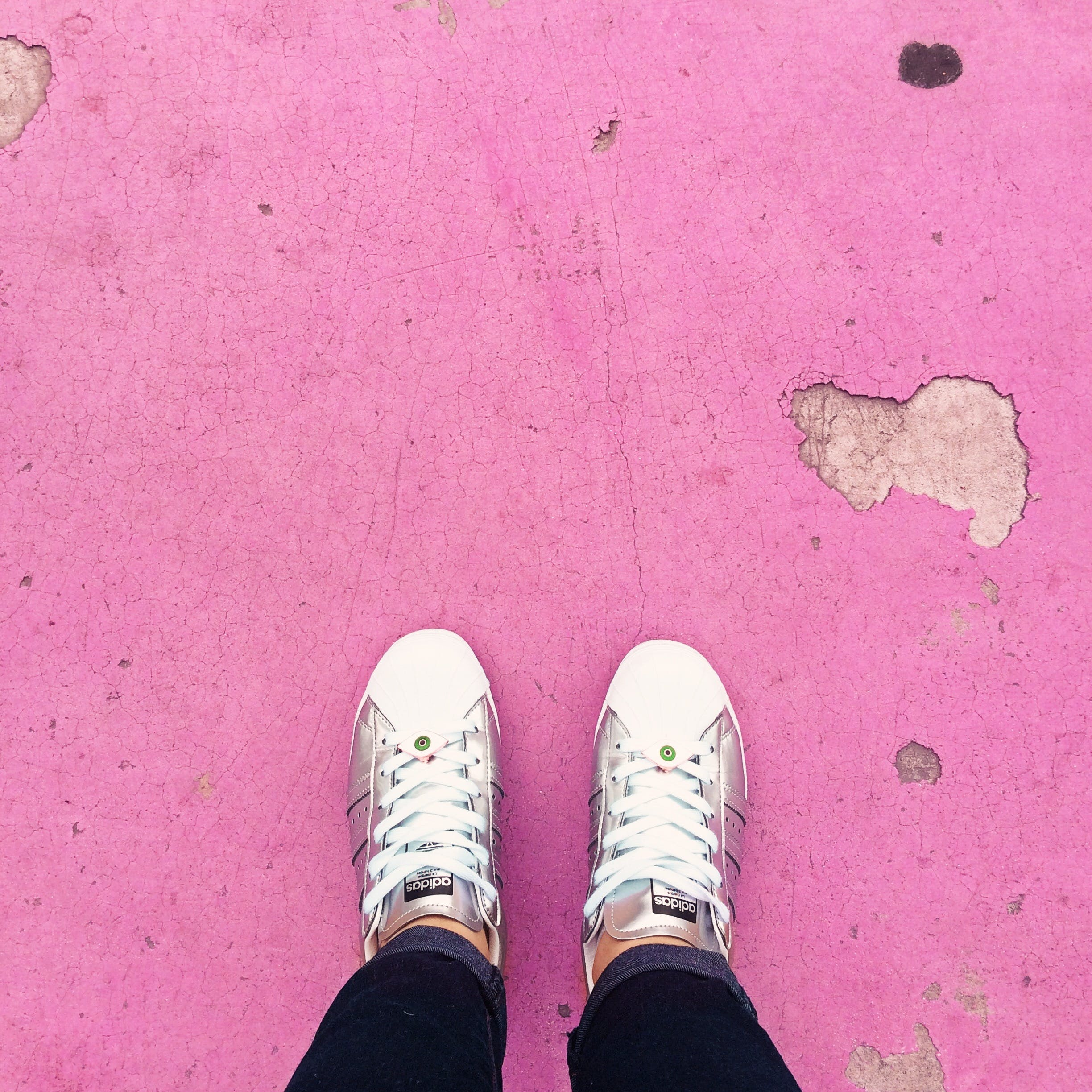 Person Wearing White Sneakers Standing on Pink Floor