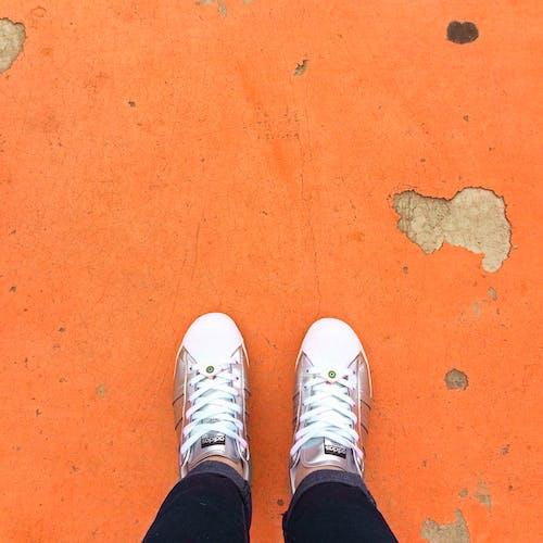 Person Wearing Sneakers Standing on Orange Floor