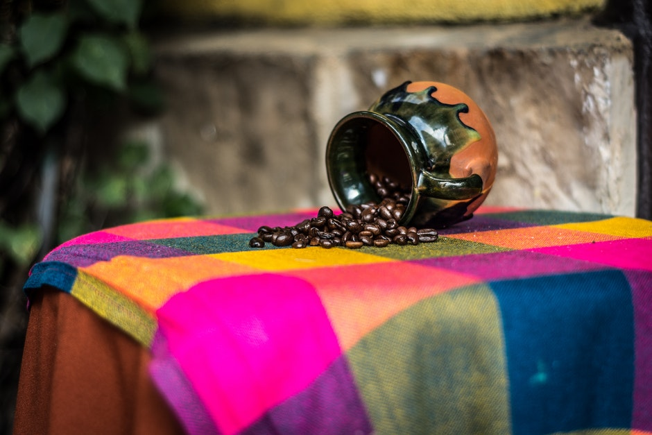 Brown and Black Ceramic Coffee Bean Rack on Pink Green and Yellow Textile
