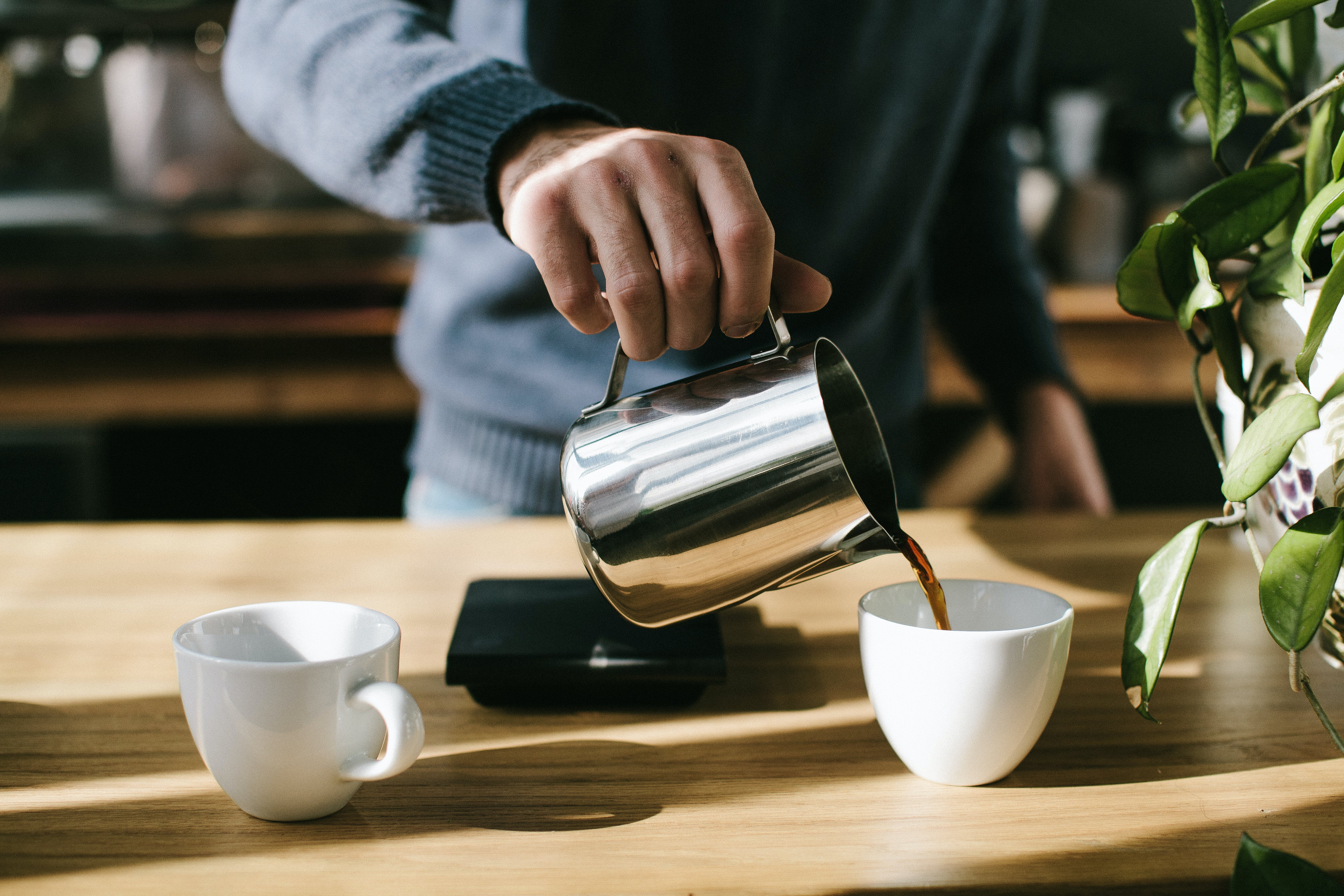 Person Pouring Coffee in White Ceramic Mug
