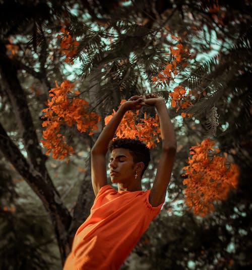 오렌지 꽃 근처 스트레칭 남자의 얕은 초점 사진
