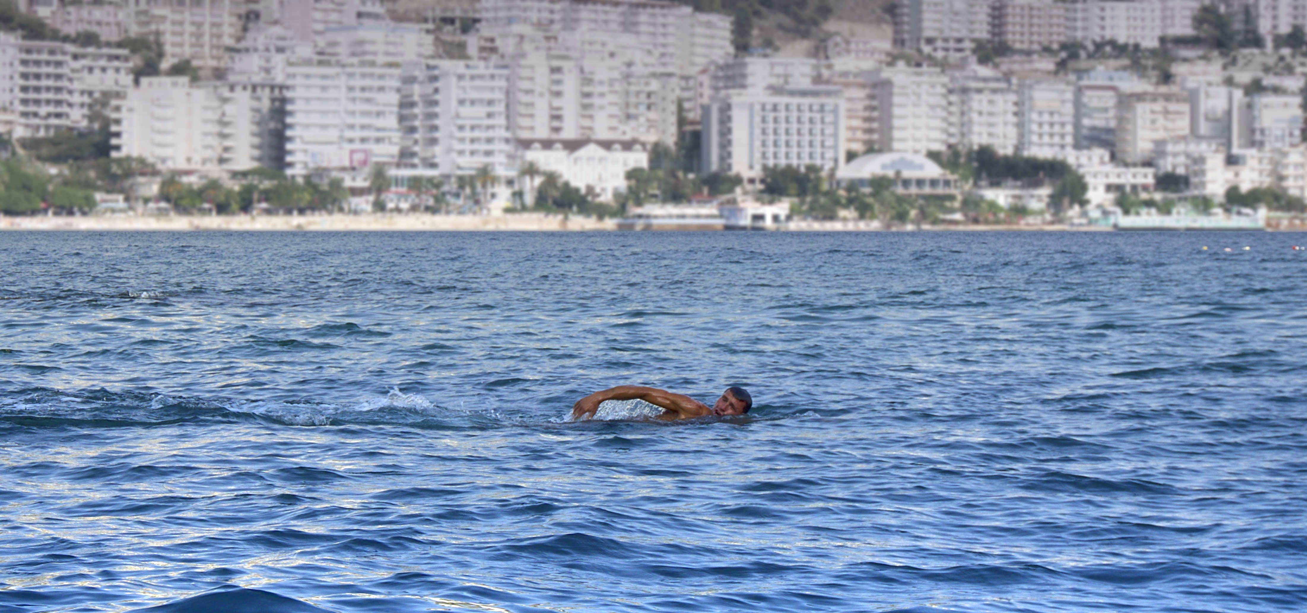 Man Swimming in a Body of Water White Concrete High Rise Building in Background