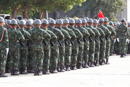 Back view unrecognizable soldiers with riffles wearing khaki uniform and hardhat lining up in rows during military ceremony