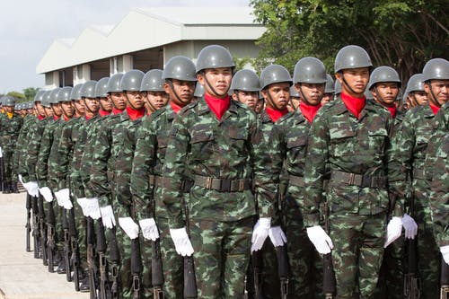 Serious ethnic soldiers lining up during military ceremony