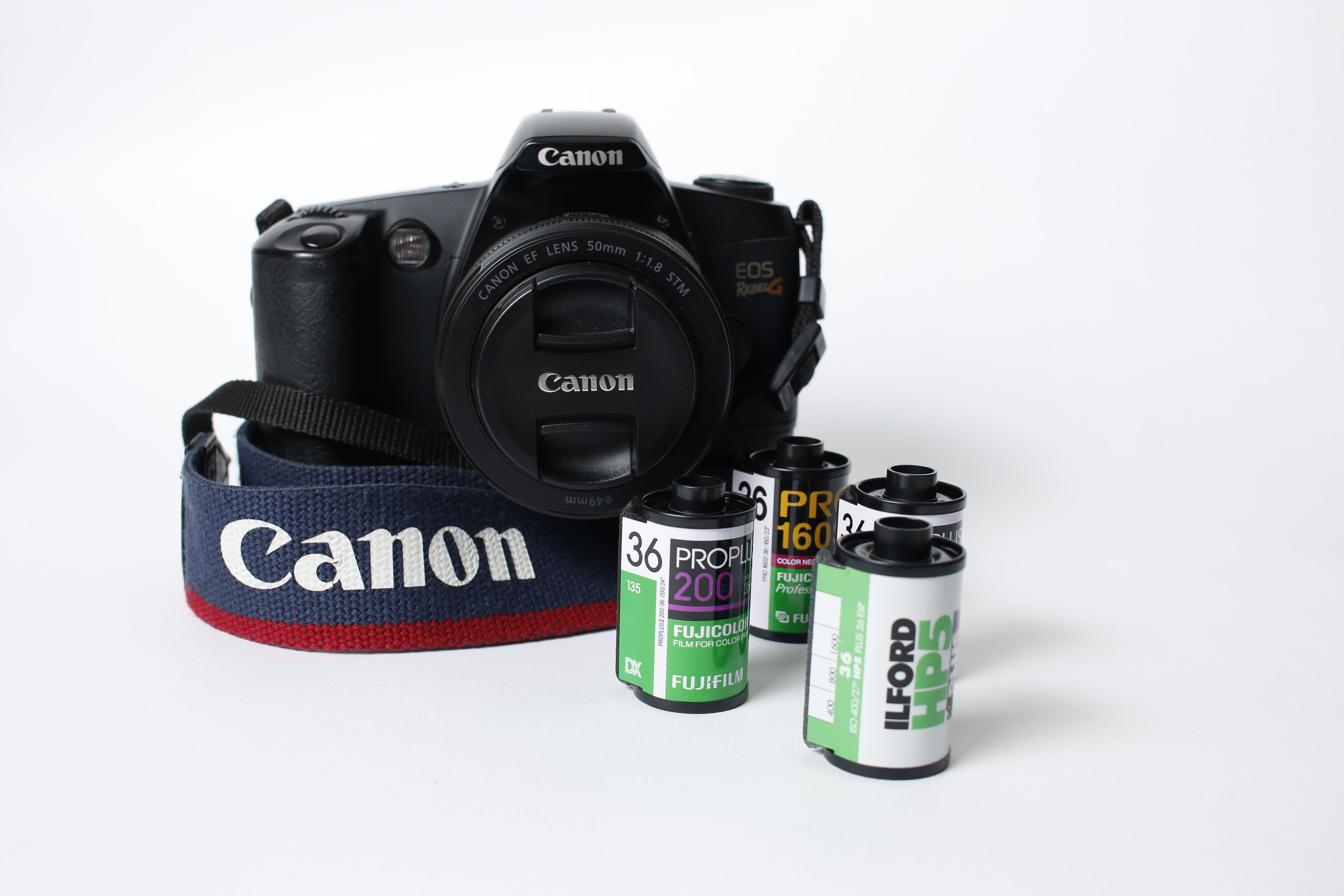 Black Canon Eos Camera Beside Four Camera Films On White Surface