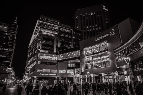 Greyscale Photography of People Walking Outside Building