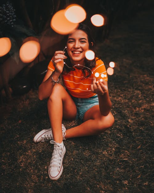 Woman Holding String Lights While Sitting On Grass