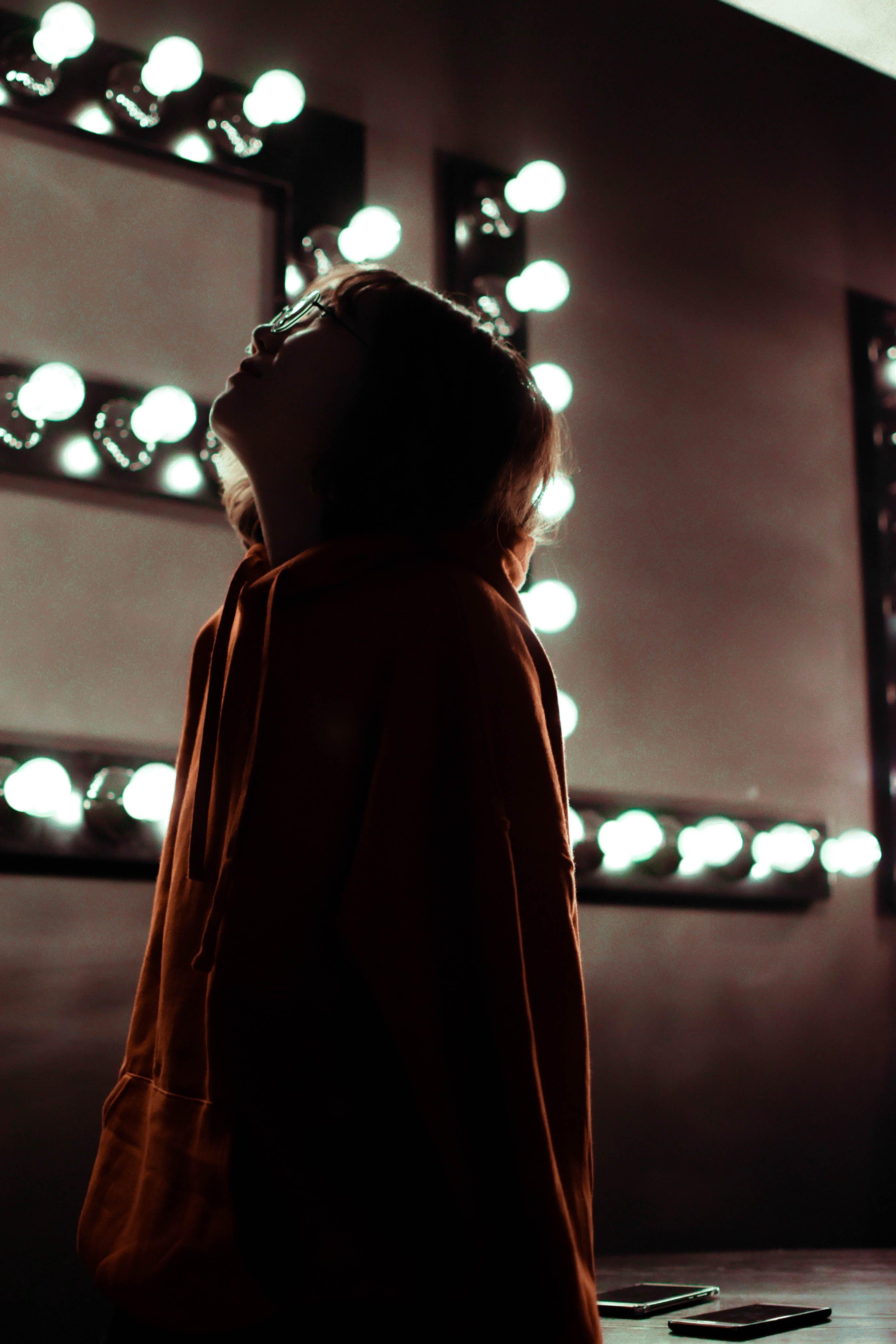 Woman Standing Near Turned-On Light Bulbs