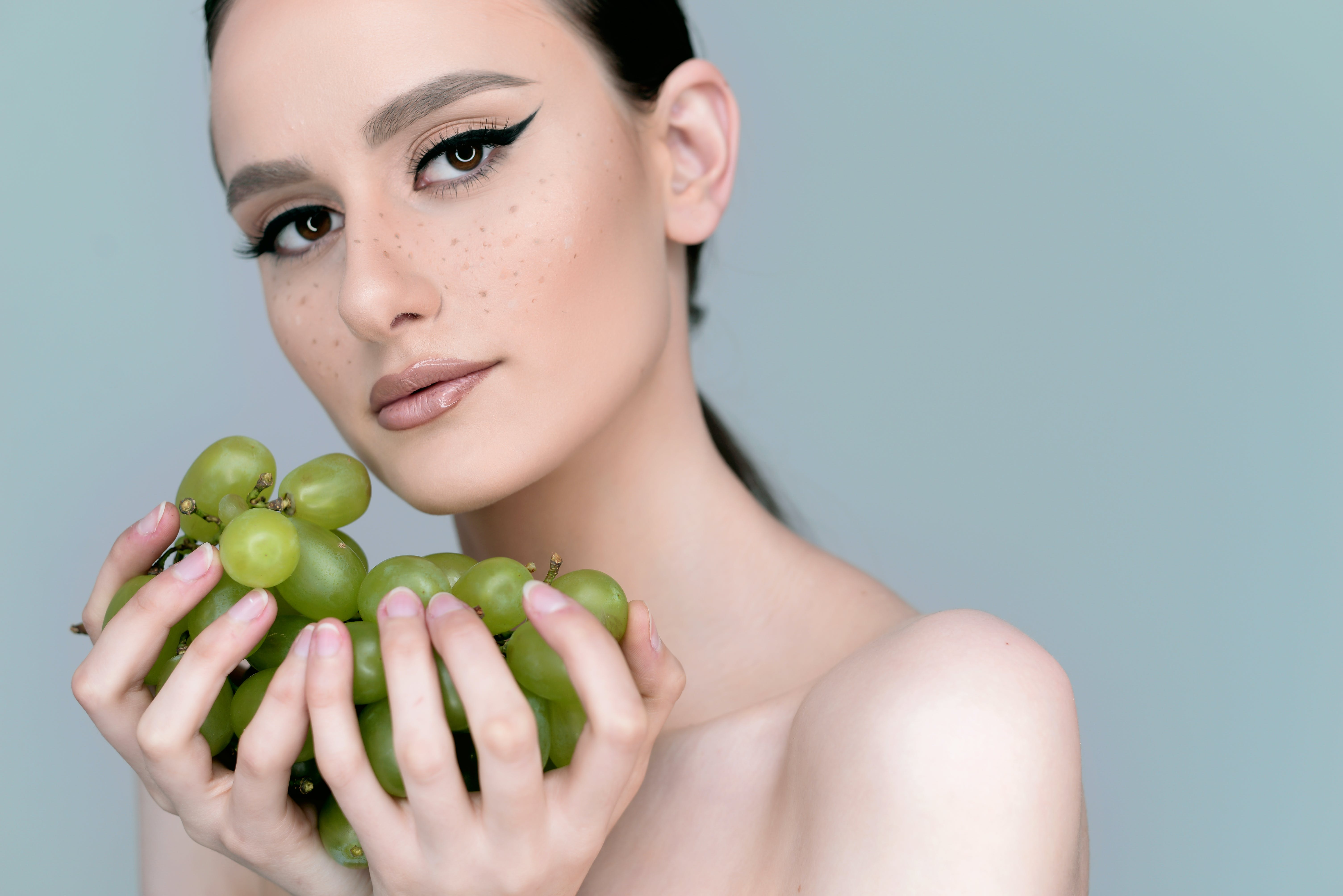 Close-Up Photo of Woman Holding Grapes